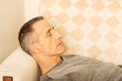 Hombre maduro que miente en el sofá Foto de archivo libre de regalías