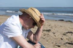 Hombre maduro que mira abajo Tomado en la playa en un día soleado Imagen de archivo