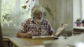 Hombre maduro que mira su álbum con las fotos viejas en casa almacen de metraje de vídeo