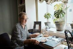 Hombre maduro que mira sus fotos viejas de la boda mientras que se sienta en hogar imagen de archivo