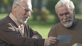 Hombre maduro que muestra las fotos de los grandchildrens a su mejor amigo, amor y orgulloso almacen de metraje de vídeo