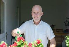 Hombre maduro que riega las flores Fotografía de archivo libre de regalías