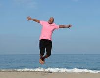 Hombre maduro que salta en la playa foto de archivo libre de regalías