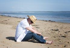 Hombre maduro que se relaja en la playa Foto de archivo libre de regalías