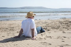 Hombre maduro que se relaja en la playa Imágenes de archivo libres de regalías