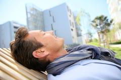 Hombre maduro que se relaja en parque público al lado de edificios Fotos de archivo libres de regalías