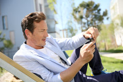 Hombre maduro que se relaja en parque residencial en suburbio Imagen de archivo