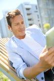 Hombre maduro que se relaja en parque usando la tableta Fotos de archivo libres de regalías