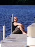Hombre maduro que se relaja en un muelle por el agua Imagen de archivo libre de regalías