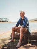 Hombre maduro que se relaja por un lago Imágenes de archivo libres de regalías