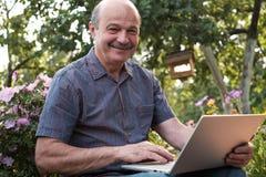 Hombre maduro que se sienta en jardín en campo con el cuaderno y que se relaja Imágenes de archivo libres de regalías