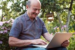 Hombre maduro que se sienta en jardín en campo con el cuaderno y que se relaja Imagen de archivo libre de regalías