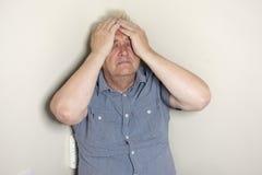 Hombre maduro que se sienta en la esquina del cuarto que parece preocupado fotos de archivo