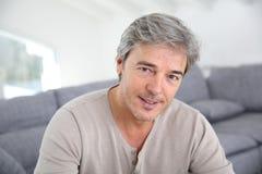 Hombre maduro que se sienta en sala de estar Foto de archivo libre de regalías