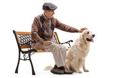 Hombre maduro que se sienta en un banco y que acaricia su perro Imagen de archivo libre de regalías