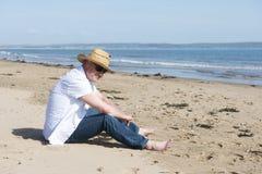 Hombre maduro que se sienta en una playa en un día soleado Fotos de archivo