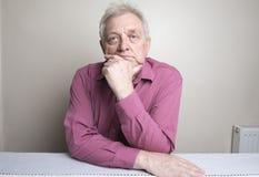 Hombre maduro que sienta abajo el pensamiento Foto de archivo