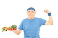 Hombre maduro que sostiene la placa llena de verduras y que muestra fuerza Imagen de archivo libre de regalías