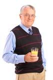 Hombre maduro que sostiene un vidrio de zumo de naranja Fotografía de archivo libre de regalías