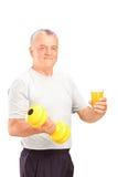 Hombre maduro que sostiene una pesa de gimnasia y un vidrio de jugo Imagen de archivo