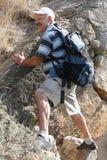 Hombre maduro que sube en roca Imagen de archivo libre de regalías