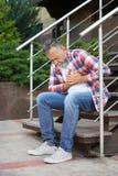 Hombre maduro que tiene ataque del corazón en las escaleras imagen de archivo libre de regalías