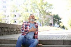 Hombre maduro que tiene ataque del corazón en las escaleras fotografía de archivo libre de regalías
