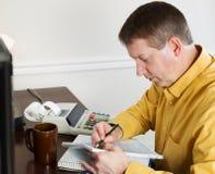 Hombre maduro que toma datos del ordenador para hacer impuestos sobre la renta Imágenes de archivo libres de regalías