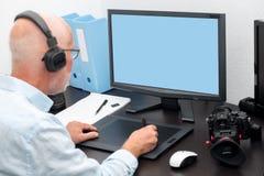 Hombre maduro que trabaja con la tableta de gráficos en su oficina fotos de archivo libres de regalías