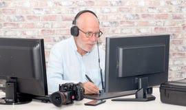 Hombre maduro que trabaja en su tableta de gráficos imagenes de archivo