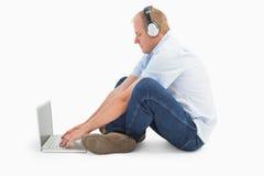 Hombre maduro que usa el ordenador portátil que escucha la música Imagen de archivo libre de regalías