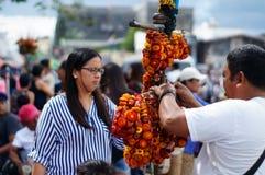 Hombre maduro que vende las flores eternas ensartadas del vendedor ambulante de la calle en una yarda de la iglesia fotos de archivo libres de regalías