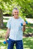 Hombre maduro sonriente con pesas de gimnasia en el parque Fotos de archivo libres de regalías