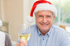 Hombre maduro sonriente en el sombrero de santa que tuesta con el vino blanco Imagen de archivo libre de regalías