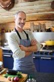Hombre maduro sonriente que se coloca en cocina Imagenes de archivo