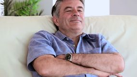 Hombre maduro sonriente que se relaja en su sofá metrajes