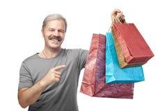 Hombre maduro sonriente que sostiene bolsos de compras aislados en blanco Fotografía de archivo libre de regalías