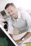 Hombre maduro sonriente que trabaja en la oficina Fotos de archivo libres de regalías