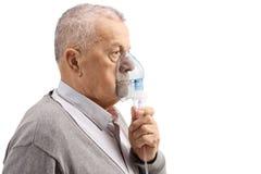 Hombre maduro usando un inhalador imágenes de archivo libres de regalías