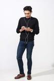 Hombre malayo que usa sus auriculares para oír música Foto de archivo libre de regalías