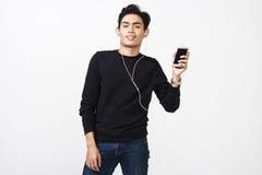 Hombre malayo que usa sus auriculares para oír música Fotos de archivo libres de regalías