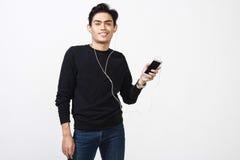 Hombre malayo que usa sus auriculares para oír música Imagen de archivo libre de regalías