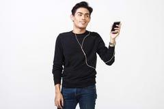 Hombre malayo que usa sus auriculares para oír música Imagen de archivo