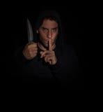 Hombre malvado que gesticula silencio mientras que sostiene un cuchillo Imágenes de archivo libres de regalías