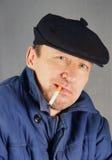 Hombre marginal en un casquillo con un cigarrillo Imagen de archivo libre de regalías