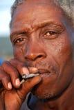 Hombre marrón que fuma Imagenes de archivo