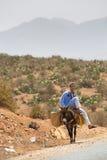 Hombre marroquí que se sienta en su burro, Marruecos imágenes de archivo libres de regalías