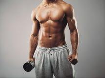 Hombre masculino en llevar a cabo pesa de gimnasia en fondo gris Imágenes de archivo libres de regalías