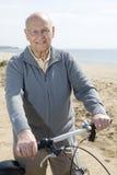 Hombre mayor activo que monta su bici Foto de archivo