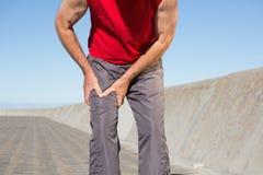Hombre mayor activo que toca su muslo herido Imagen de archivo libre de regalías